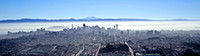 Panoramic aerial view of downtown San Francisco with Treasure Island and the Port of Oakland just visible in the early morning fog