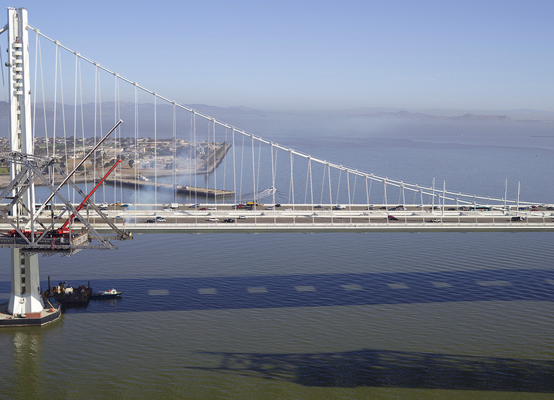 The old span of the bay bridge being removed with the new span in the background