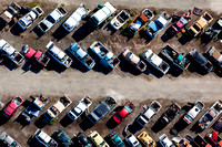 Scrap yard cars laid out  in a herringbone pattern shot from a helicopter